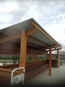 Covered timber seating for bowlers with colorbond roof