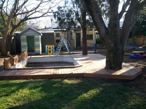 Timber decking around kindergarten sandpit